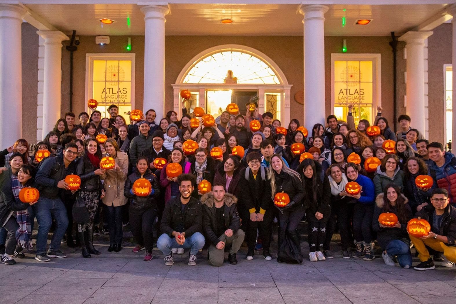 Students with carved pumpkins in front of the school